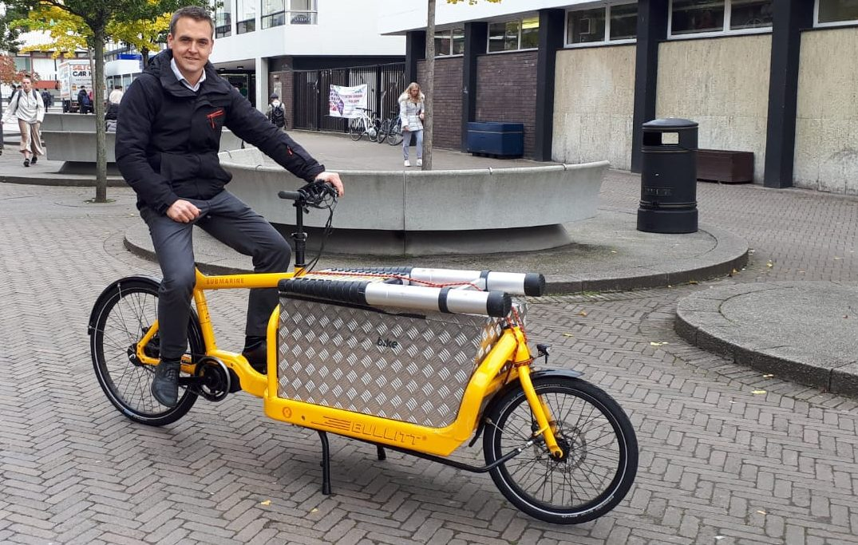 Tom Crone sitting on electric cargo bike